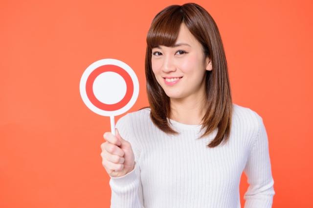 女性が丸のカードを持ている写真